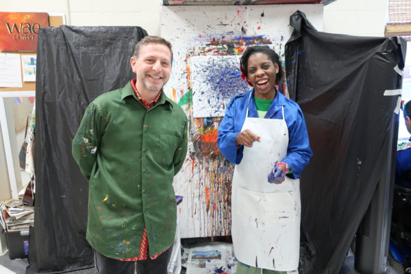 Mishawn and Adam Swart pose in front of her splatter painting.